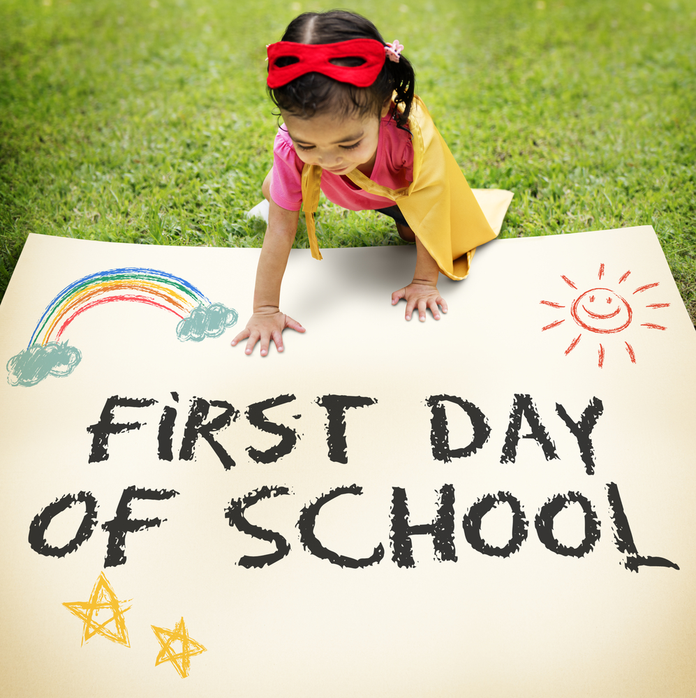 Child holding sign that reads first day of school